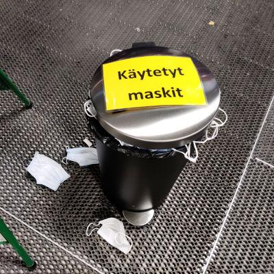Käytettyjä maskeja pursuava roskakori.