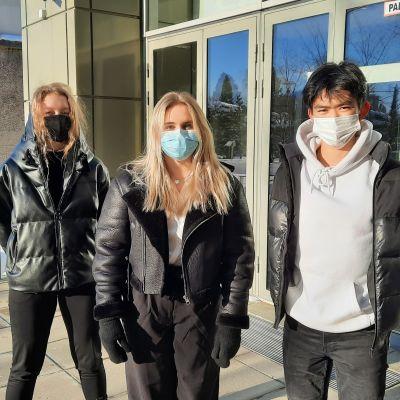 Tre ungdomar med munskydd står utanför en skolbyggnad.