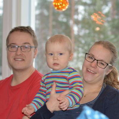 En familj sitter i soffa. En man och en kvinna och ett sju månader gammalt barn.Barnet är i mammans famn.  Alla ler.