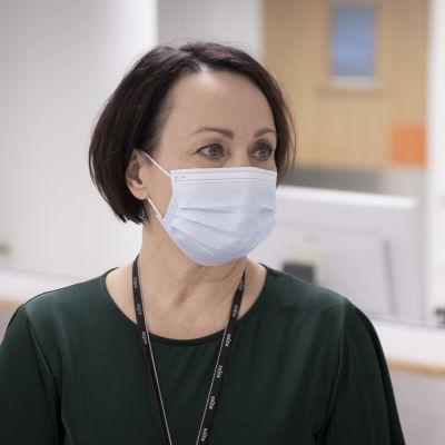 Mörkhårig kvinna med munskydd.
