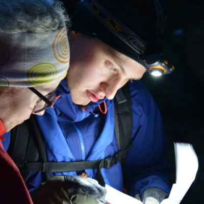 """Två ungdomar, Emma Liljeroth och Sebastian Nastamo, studerar en karta med nattlampor i mörkret på scouttävlingen Sök och Finn. Tävlingens motto är """"En tanke sparar tusen steg"""""""