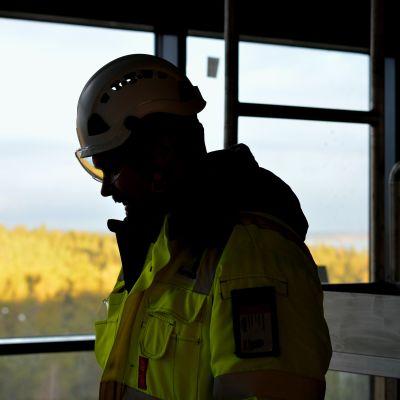 Siluetten av processkötare Ronnie Gustafsson inne på nyaste fabriken på Fermions fabriksområde i Hangö. I bakgrunden utsikt över skog.