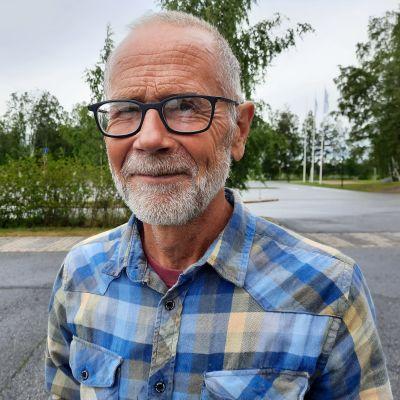 En skäggig man med glasögon och rutig skjuta står ute på asfalt.