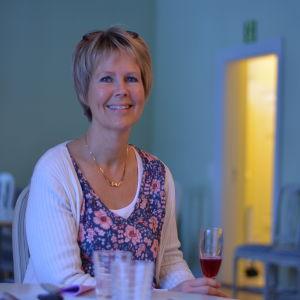 Birgitta Udd sitter med ett saftglas i handen.