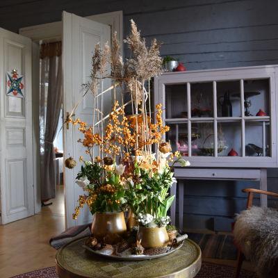 Floristik jularrangemang med gula färger och magisk snö.