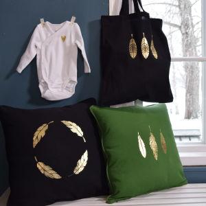 två kuddar, en väska och en babybody med guldtryck