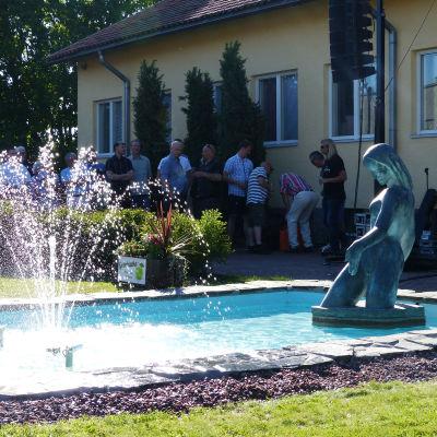 En bild på en fontän. I bakgrunden syns människor och fontänen är omgiven av gräs och buskar. I fontänen finns en staty.