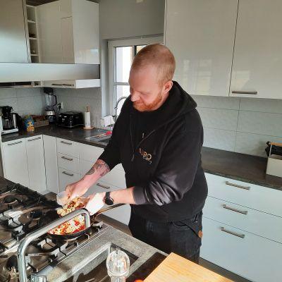 Eemeli Liljeström lagar mat i sitt kök.