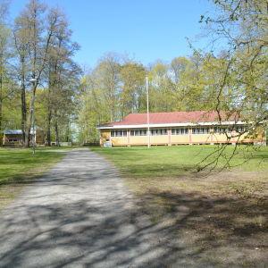 En bred, men ganska låg gulmålad träbyggnad ute i grön och lummig natur. I bakgrunden syns också en mindre gul träbyggnad.