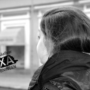 Ung kvinna med långt hår i höstsvans tittar bort från kameran