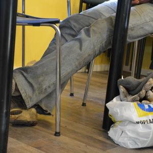 En hemlös person i slitna kläder sitter vid ett bord.