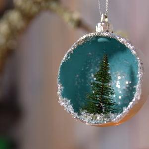 Joulukuusen pallo jossa sisällä pieni kuusi.