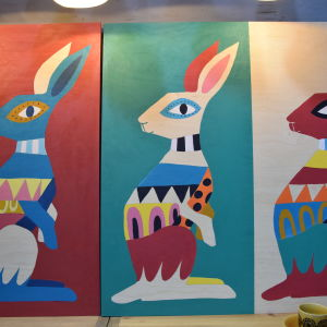 Målning av tre harar med geometriska former.