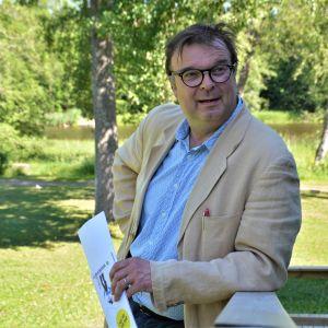 Man i skjorta och kavaj lutar mot en ledstång på en trappa utomhus. I handen har han en broschyr. I bakgrunden gräsmatta, träd och en sjö.