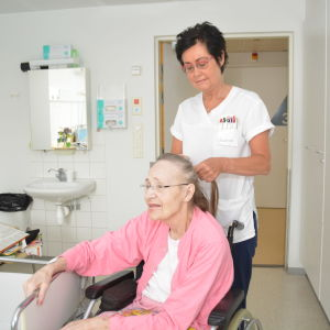 Susanne Enholm kammar Gullevi Silfvast hår på bädden i Hangö.