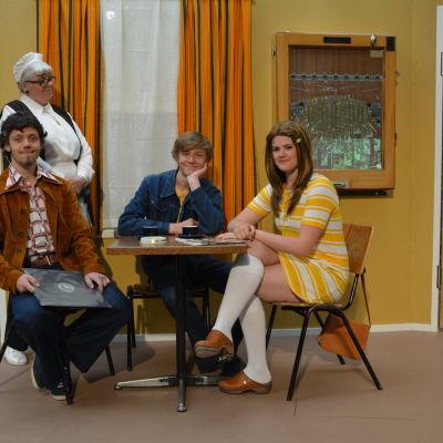 """William Stocks, Filip Hartman och Mecki Ruokolahti spelar några ungdomar som hänger på Axos bar. Skini Lindgård spelar Axo-tanten """"Hököga"""" / Berit."""