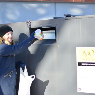 Malin Kurkisuo slänger plastavfall i en kontainer.