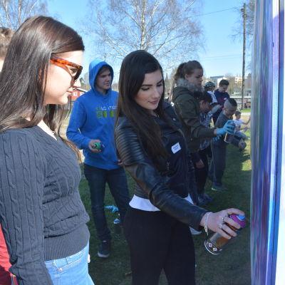 Hannah Hasselberg målar graffiti på Raseborg offspring 2016. Jennifer Augutsson ser på.
