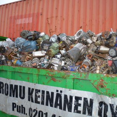 Metallskrot i en grön container. Det stor Romu Keinänen på containern.