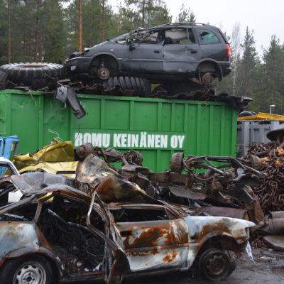 Skrotbilar på en industrigård. Där finns också annat metallskrot. I mitten en stor grön container som det står Romu Keinänen på.