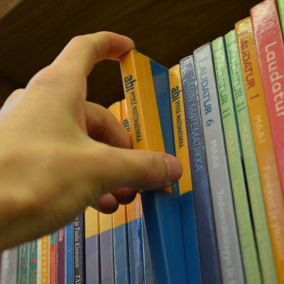 Bild på en hand som rör vid gymnasieböcker