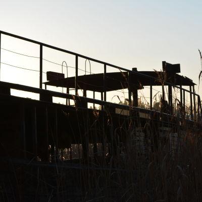 profilbild av skrotbåten i solnedgång.