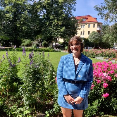 Studerande Agnes Lindberg står framför en blommig park i Helsingfors.