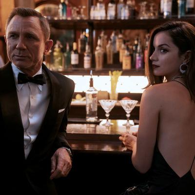 Bond i smoking stående vid en bardisk med kvinna i vacker klänning.