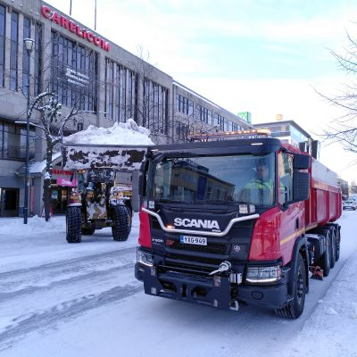 Traktori nostaa lunta kuorma-auton kyytiin.