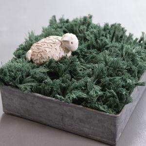 Påskgräs gjort av garn med ett keramikfår som pynt