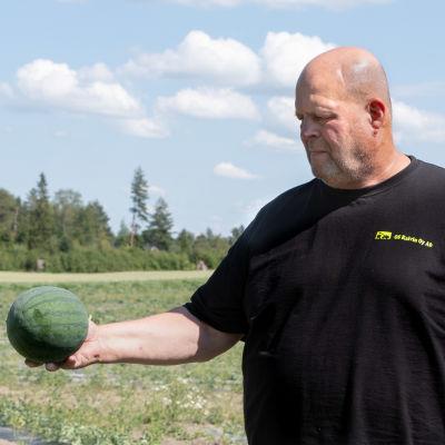 En man håller i en vattenmelon, vädret är soligt och åkrar syns i bakgrunden.
