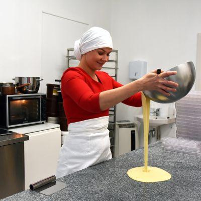 Kvinna häller smält vitchoklad på en granitskiva.