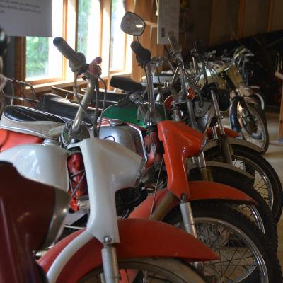 Gamla mopeder i lång rad inne i en hall som fungerar som museum.