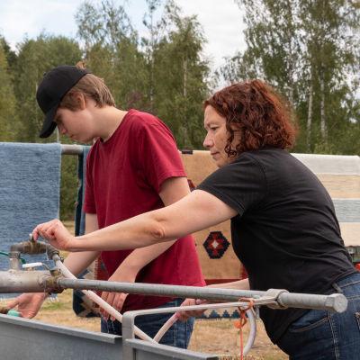 En kvinna och en pojke sträcker sig efter kranen vid en stor balja, de tvättar mattor.