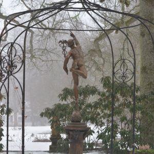 En skulptur av en man som pekar fingret mot himlen som står i en fontän i ett vinterlandskap.