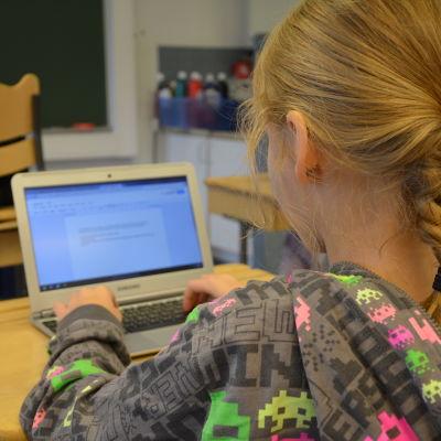 En flicka sitter i en skolbänk och skriver på sin lärplatta.