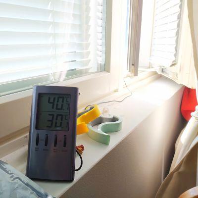 Termometer visar 30 grader vid soligt fönsterbräde och persienner för fönstren.