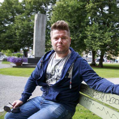 Jussi Parkkila sitter på en parkbänk