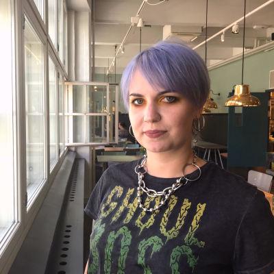 Kvinna med kort violett hår poserar vid fönster i café