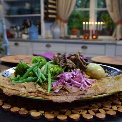 Serveringsfat med etiopisk injera med Doro Wat-kycklinggryta