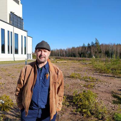 En man bredvid en vit byggnad och tom tomt.