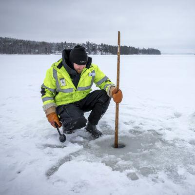 Vesitaloussuunnittelija Tarmo Muuri Etelä-Savon ELY-keskuksesta mittaa jään paksuutta Pyhäveden jäällä.