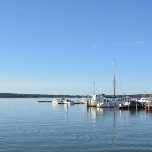 Båtar ligger förtöjda vid en brygga. Solen skiner och havet ligger stilla.