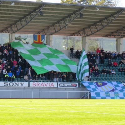 IFK Mariehamn-supportrar på läktare med grönvit flagga.