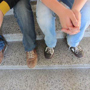 Två killar sitter i trappa i skolan.