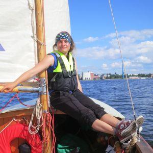 Kvinna med flytväst sitter i fören av en segelbåt.