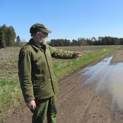 Jordbrukare Nisse Husberg tittar ut över sina fuktiga åkrar. Meteorologen lovar mera regn.