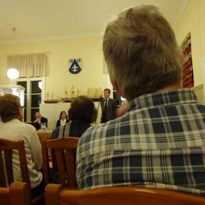 Publik lyssnar på tre Aktiachefer i en sal på Stämbacken i Pojo.