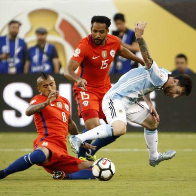 Chilen Arturo Vidal  ja Argentiinan Lionel Messi taistelevat pallosta.