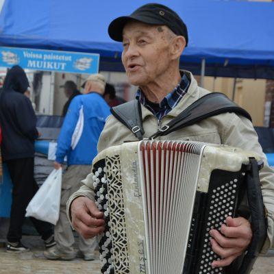Man som spelar dragspel på Strömmingsmarkanden i Vasa.